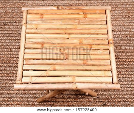 Natural bamboo folding table on jute pile hand woven area rug