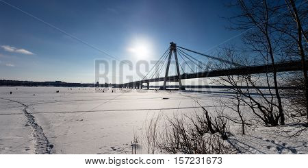 Panoramic view of cable-stayed pipeline in Chrepovetz, Russia in winter sunny day. Group of skiers and fishermen at the distance.