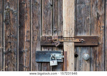 Old Wooden Door Latches with Locks. Locked Door with Padlocks.