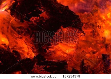 Embers closeup. Embers after a fire. Glowing embers. Glowing embers in hot red color
