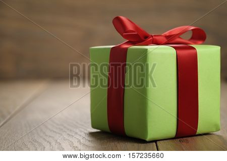 simple green paper gift box with red ribbon bow on oak table with copy space, shallow focus