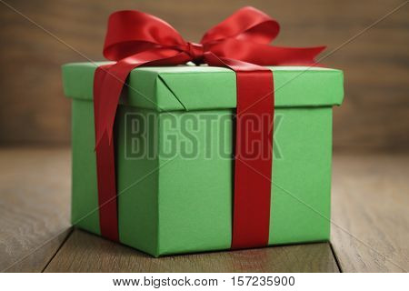 green paper gift box gift box with lid and red ribbon bow on wood table, shallow focus