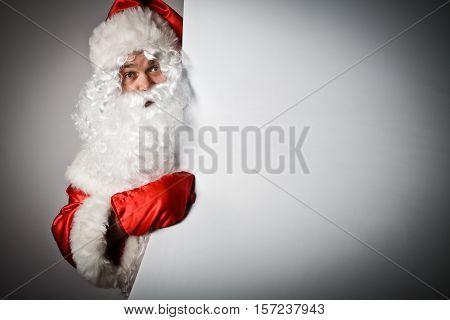 Santa Claus is pointing at billboard. Christmas.