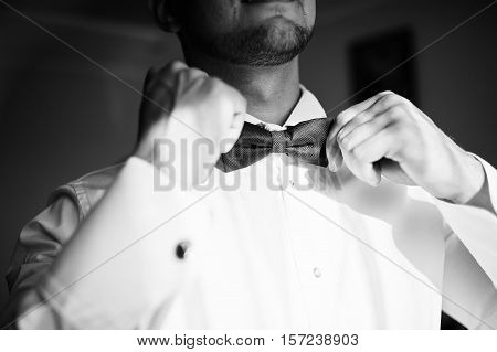 Man Wearing Bow Tie On Shirt. Gathering Of Groom On Wedding Day. Black And White Photo