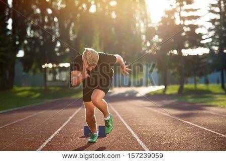 Sprinter leaving starting blocks on the running track. Explosive start