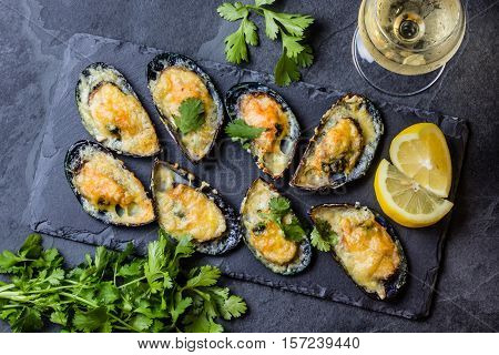 Seafood. Shellfish mussels. Baked mussels with cheese, cilantro and lemon in shells on slate stone board.