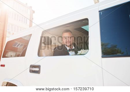 Handsome Groom Sitting On White Limousine And Looking From Window Of Car.
