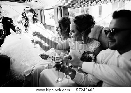 Stylish groomsman or best man of groom and bridesmaids with wedding couple inside limousine at wedding party drinking champagne. Black and white photo