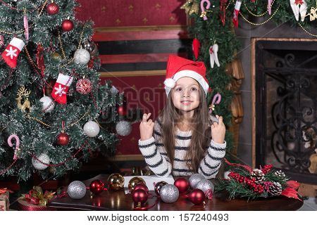 Beautiful girl in red Santa hat makes a wish at Christmas, fingers crossed.