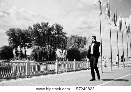 Elegant Groom On Sunglasses Walking Waterfront Of Lake With Flag Mock Up At Sunny Wedding Day. Black