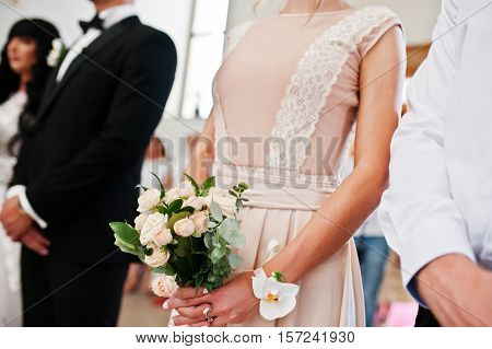 Wedding bouquet on hand of bridesmaid on church at wedding ceremony.