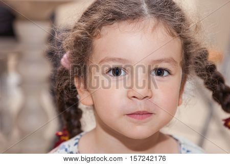 Portrait cute curly baby girl with pigtails closeup indoors tricky glance