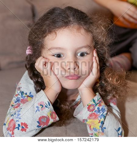 Cute little girl with curly hair brown eyes lying on the bed propped up hands head thoughtful dreaming offended resentment depression loneliness