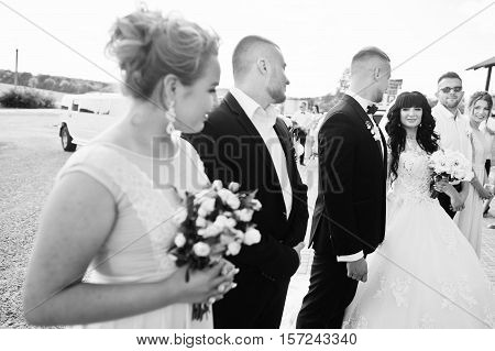 Wedding Couple And Bridesmaids With Best Mans Background Wedding Quests. Black And White Photo