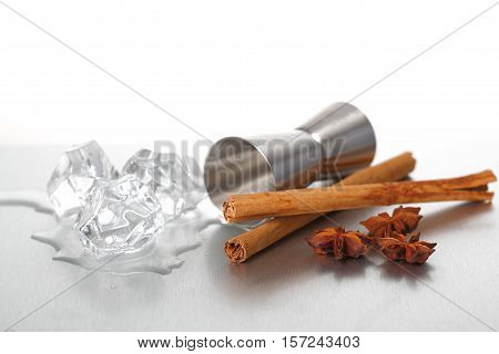 Jigger, melting ice cubes and spices on a stainless steel surface.