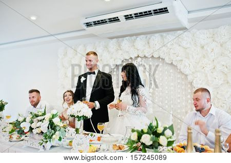 Wedding Couple With Glasses Of Champagne Stay Near Table At Restaurant.