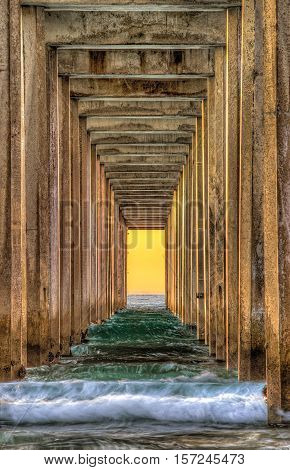 Symmetrical shot under Scripps Pier with waves during sunset in La Jolla, San Diego, California