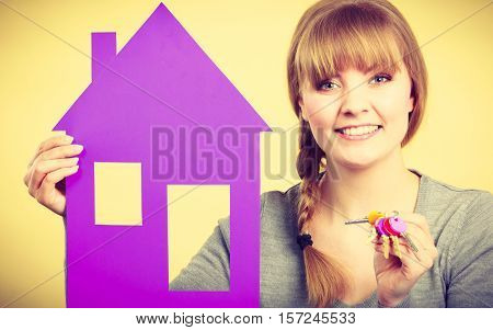 Ownership and property concept. Young blonde smiling female owner with bunch of colorful keys and house.