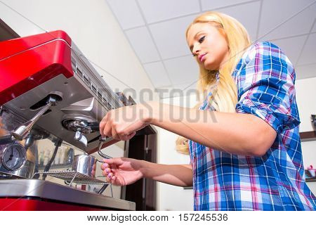 A beautiful young woman making coffee at the bar in a coffee shop