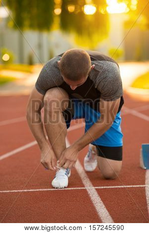 Young Man Runner tying his shoes on a running track. Shoelaces, Urban jogger.