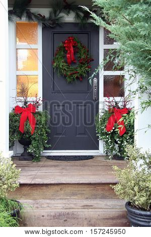 Front door with a Christmas wreath and bows.
