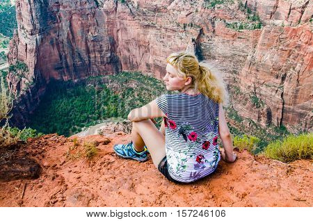 Young woman sitting on edge on top of canyon on Observation Point trail in Zion National Park