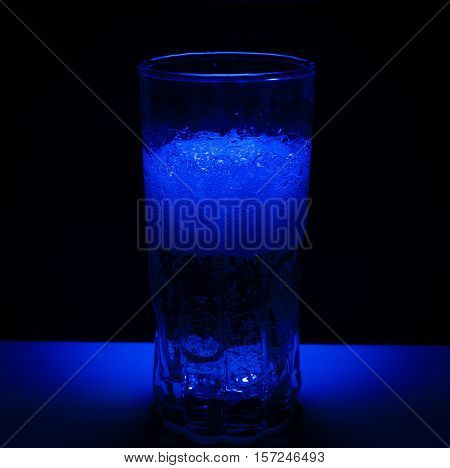 A half full drink with bubbles in blue light and dark bakground