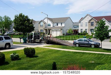 JOLIET, ILLINOIS / UNITED STATES - MAY 24, 2016: A tow truck prepares to remove a disabled vehicle in the Wesmere Country Club subdivision of Joliet.