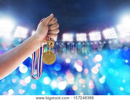 Win concept. Man holding up a gold medal against is winner in a competition in night stadium.