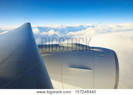 air plane engine and wing floating over white cloud and blue sky