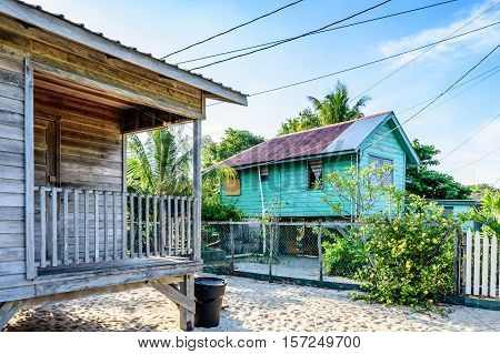 Wooden houses on sand next to Caribbean beach in Belize, Central America