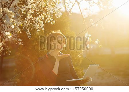 Cute girl student holding a laptop in hand. Portrait against the setting sun and cherry blossoms. She sends a kiss on the Internet. Warm toning. Videophone.
