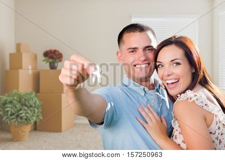 Happy Young Military Couple with House Keys in Empty Room with Packed Moving and Potted Plants.