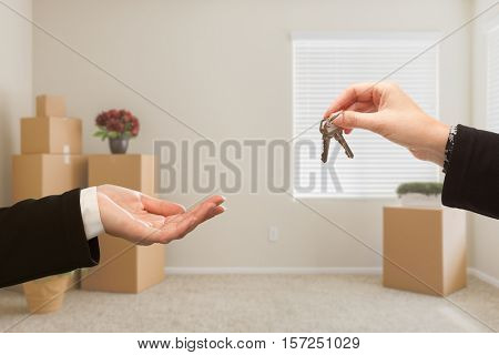 Woman Handing Over House Keys In Room with Packed Moving Boxes.