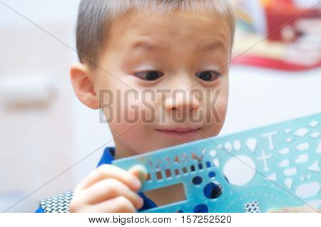 Amazed boy surprized face with interesting ruler