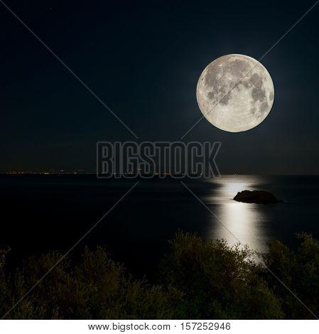 night scene. full moon reflected on the sea. city lights on the horizon.