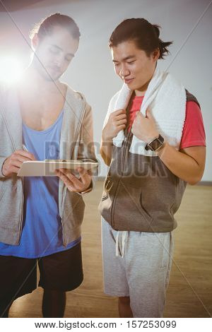 Fitness trainer guiding hid trainee on clipboard in gym