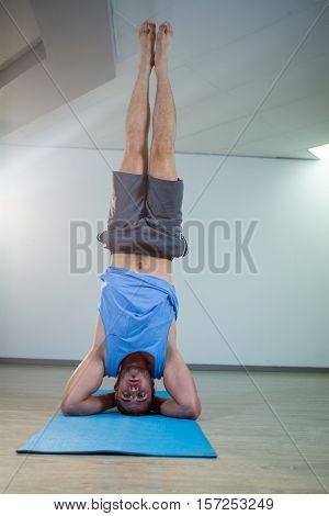 Man performing sirsasana on exercise mat in gym