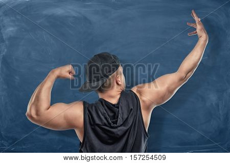 Back view portrait of a fit athlete flexing and stretching arm muscles on the dark blue background. Sport and healthy lifestyle. Keep fit. Athletic body. Exercises and warming up.