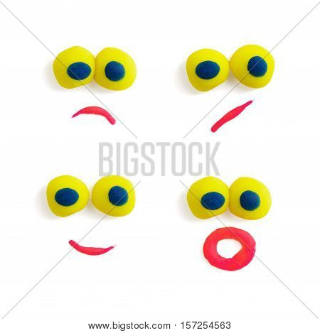Four funny faces - eyes and mouths - made of multicolored plastic with different expressions on the white background. Art and fun. Kid's games and activities. Handmade objects. Face expressions.