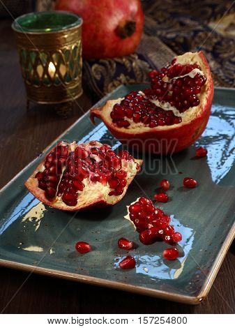 The opened fruit of ripe pomegranate lies on a dish