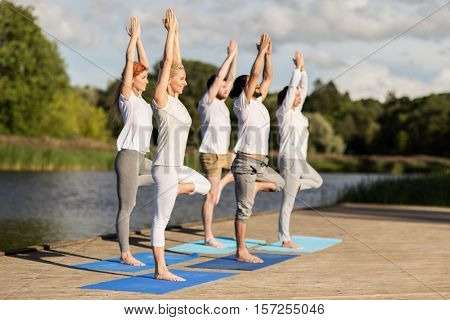 yoga, fitness, sport, and healthy lifestyle concept - group of people in tree pose on mat outdoors on river or lake berth