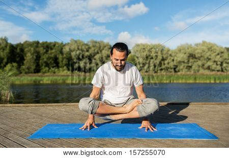 fitness, sport, yoga, people and healthy lifestyle concept - man making scale pose lotus variation on mat outdoors on river or lake berth