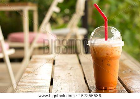 Ice thai milk tea drink / Iced milk tea on wooden table