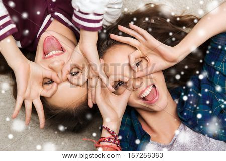 people, friends, winter, christmas and friendship concept - happy smiling pretty teenage girls having fun and making faces over snow