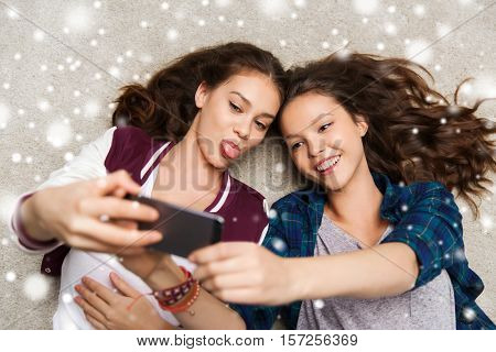 people, technology, winter, christmas and friendship concept - happy smiling pretty teenage girls or friends lying on floor and taking selfie with smartphone over snow
