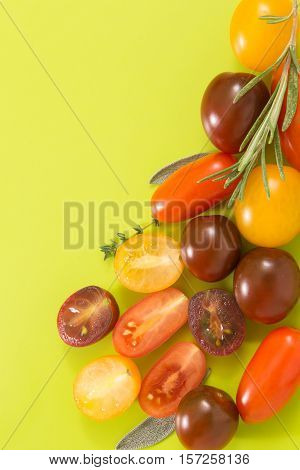 Colorful Cherry Tomatoes Cluster With Herbs, On Chartreuse Yellow Background With Copy-space