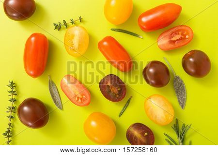 Colorful Cherry Tomatoes With Herbs, On Chartreuse Yellow Background.