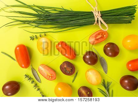 Colorful Cherry Tomatoes With Chives And Herbs, On Chartreuse Yellow Background.