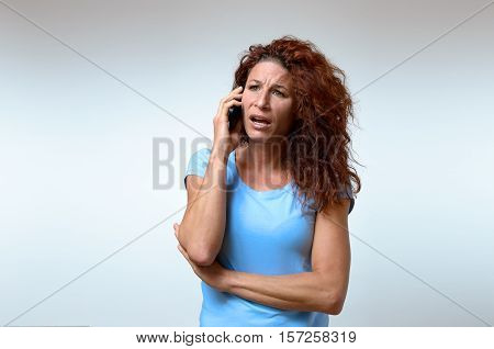 Young woman receiving bad news on her mobile listening to the call with a look of horror and consternation upper body on white